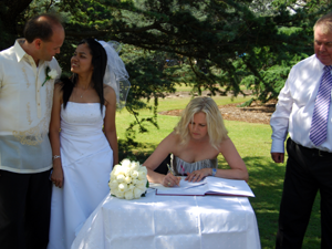 The happy couple wait for their witness to sign the register